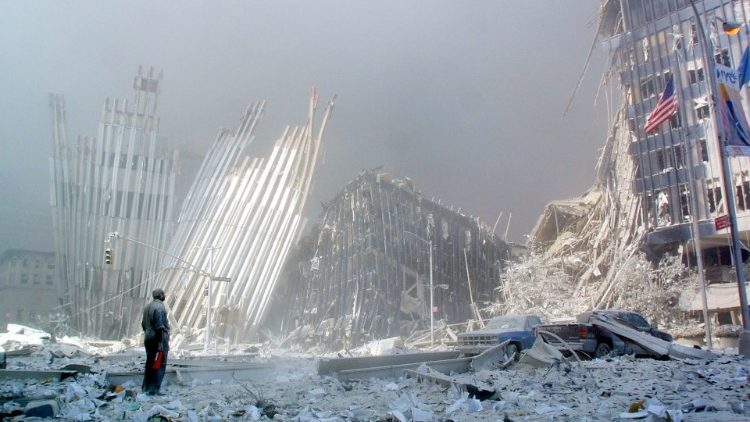 A survivor stands in front of the wreckage of the World Trade Center on September 11, 2001